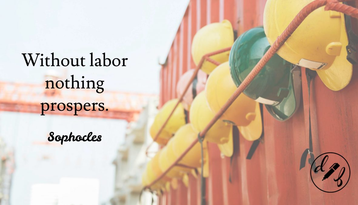 A row of hard hats hanging on a red wall outside with a quote by Sophocles