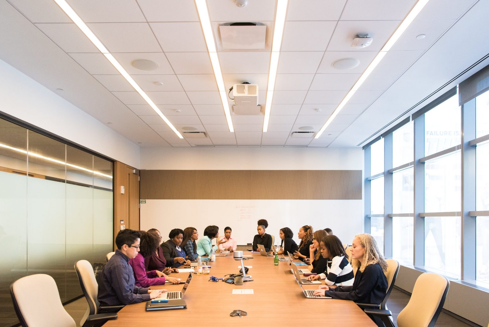 Women in a warmly lit boardroom with laptops