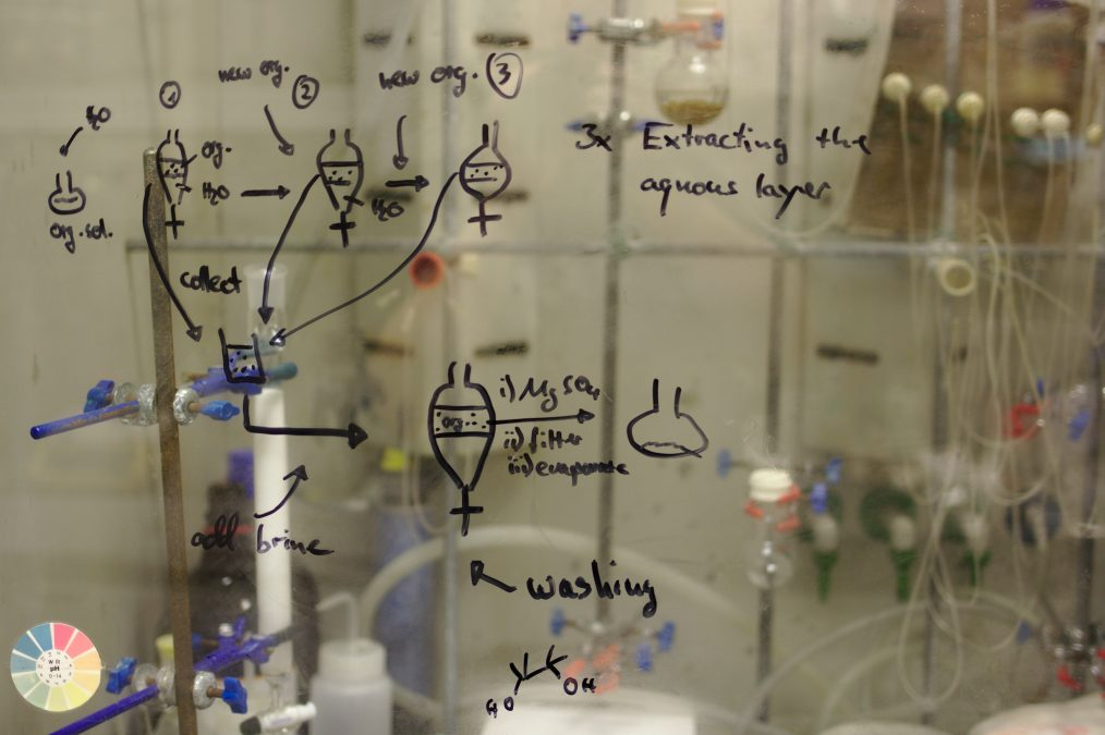 Equations written with a black dry erase marker on a glass in a lab setting