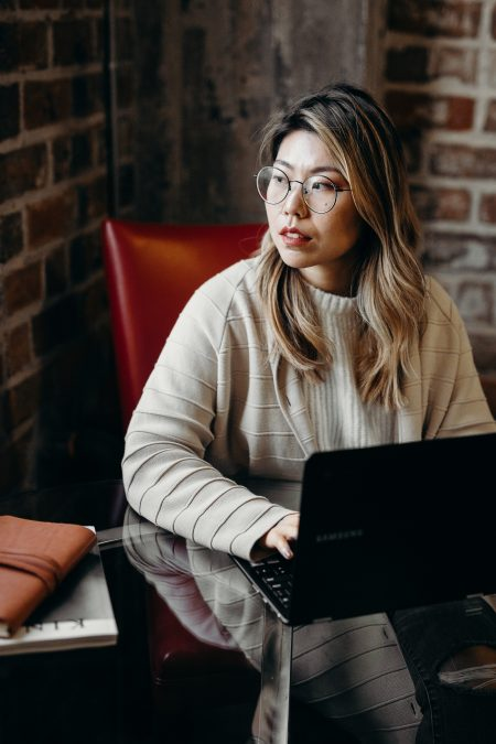 An East Asian woman in a cream sweater and glasses looks sideways while sitting down at a black laptop computer. Mental Health.