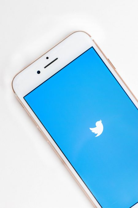 A gold iPhone displaying a Twitter logo