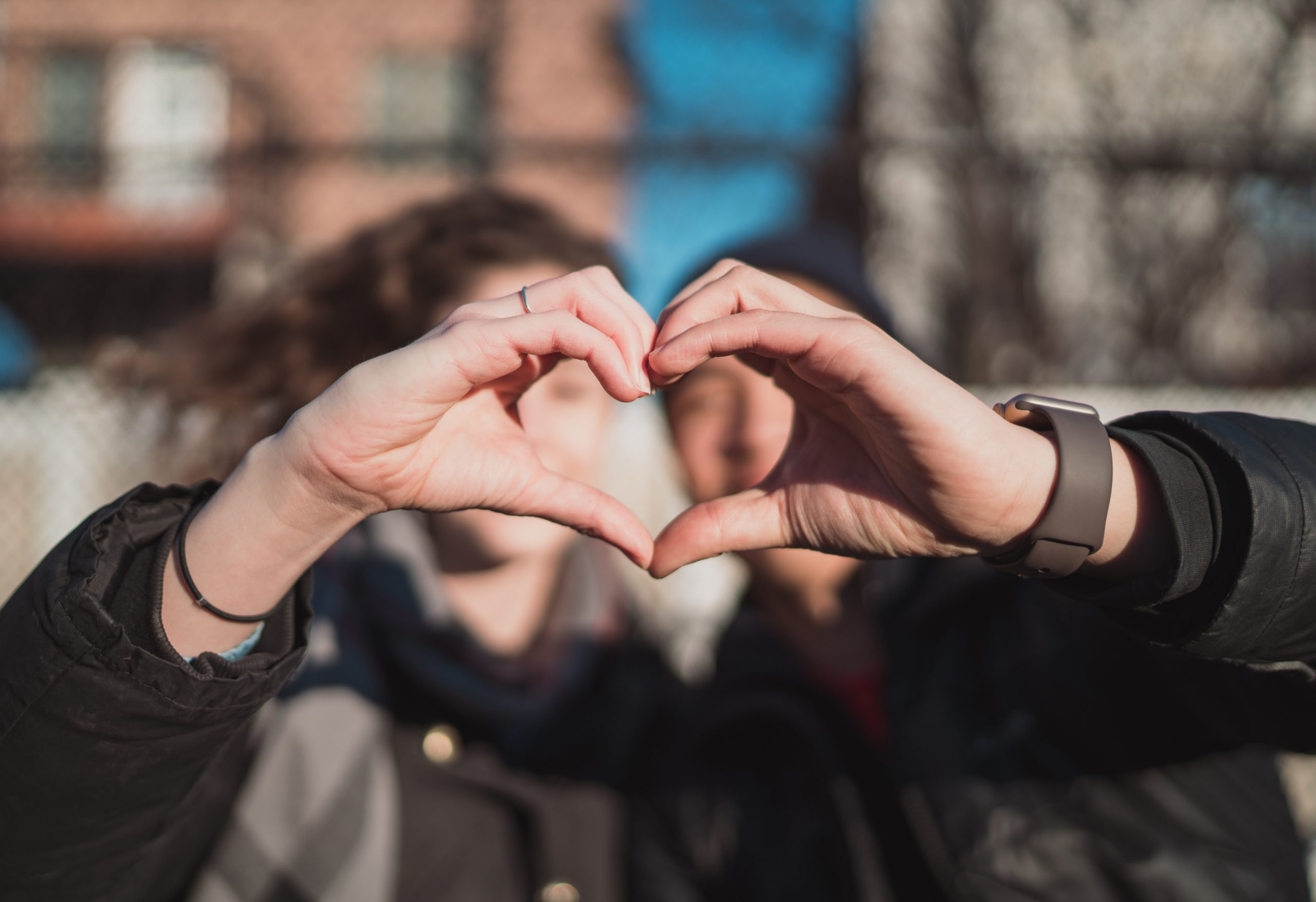 Two people hold their hands up to form a heart