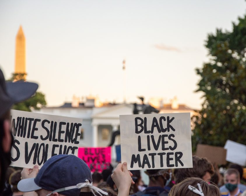 "A Black Lives Matter protest outside of the White House. Proteters hold signs that say ""WHITE SILENCE IS VIOLENCE"" and ""BLACK LIVES MATTER"""