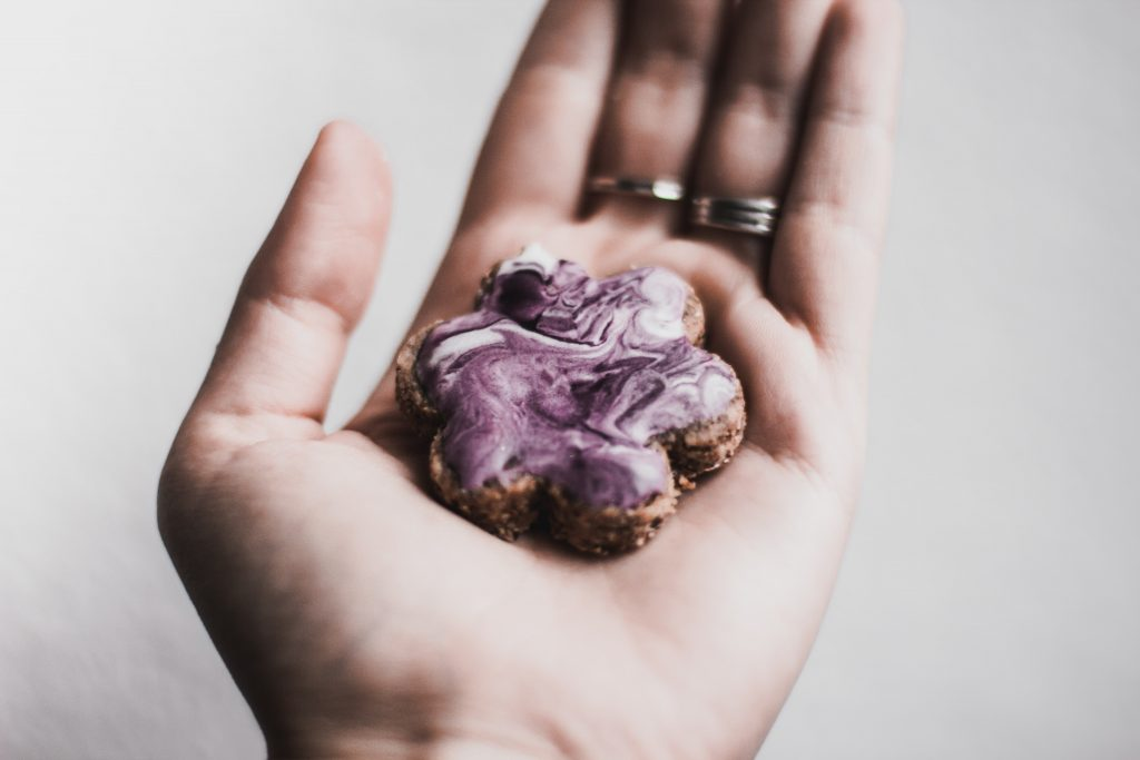 A purple and white cookie in someone's hand - tasty, customized solutions