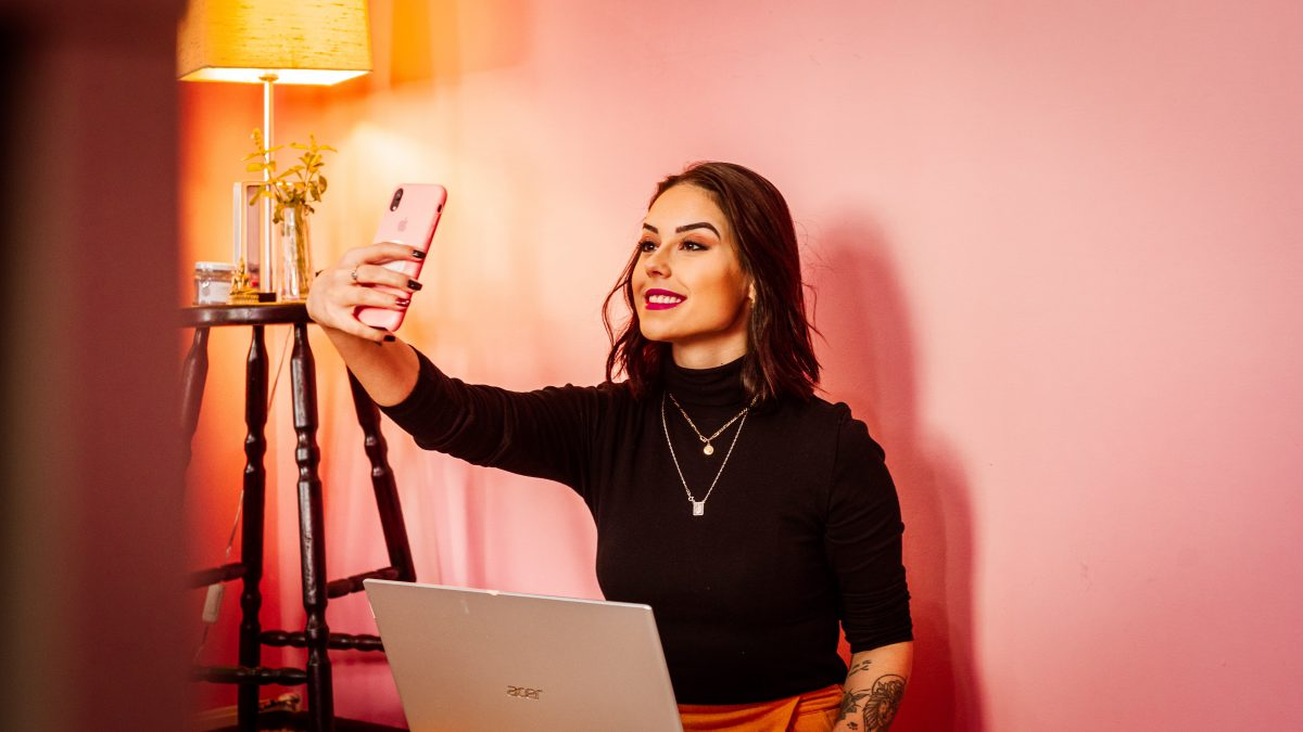 Influencers have been accused of not being authentic, and for good reason. A woman holds out her pink cellphone and smiles into it.
