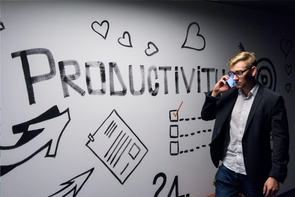 A white man with glasses, a white button-up shirt, a black blazer, and jeans is walking with a phone to his ear. To his right is a white board with big black block letters that say PRODUCTIVITY